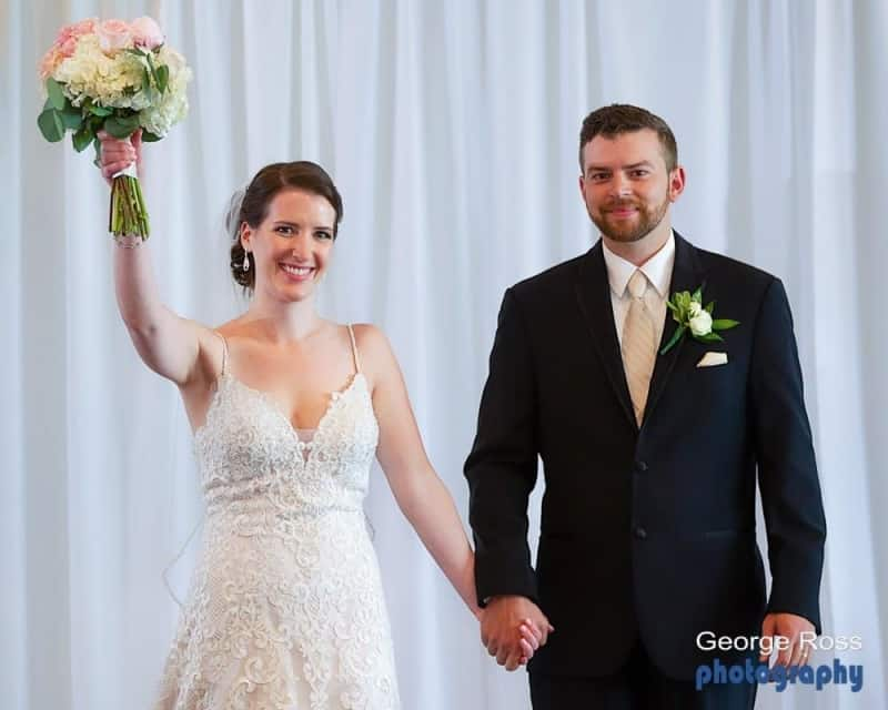 wedding ceremony, bride and groom walk down the aisle after the ceremony with the bride raising her bouquet