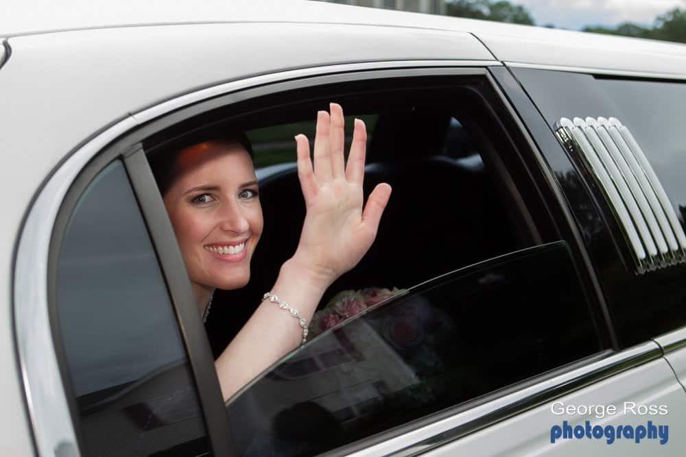 bride waving out of the window of the bridal limousine