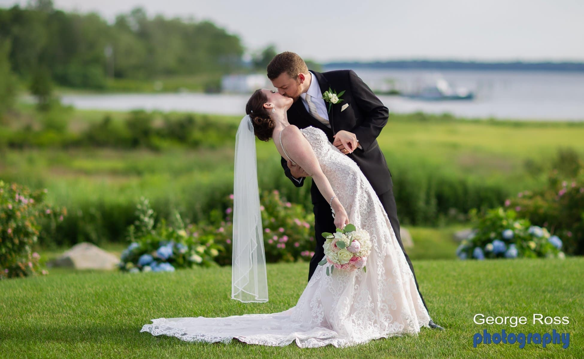 Groom dips his bride while kissing her, in a beautiful setting at harbor lights, Warwick, rhode island