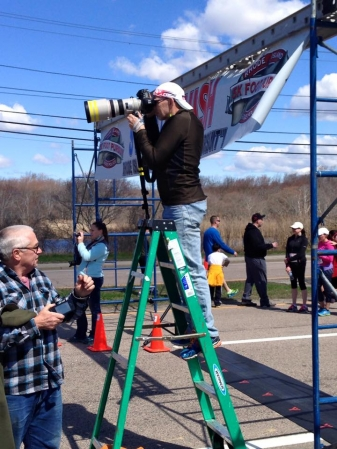 photographer standing on a step ladder to photograph a road race
