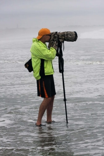 a photographer standing in the ocean with a monopod shooting surfers on narraganset beach, rhode island