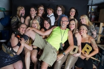 Photographer george ross have fun with a large group of roller derby players after a photoshoot