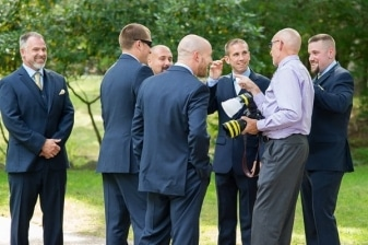 wedding photographer sharing a joke with the groomsmen before the wedding ceremony