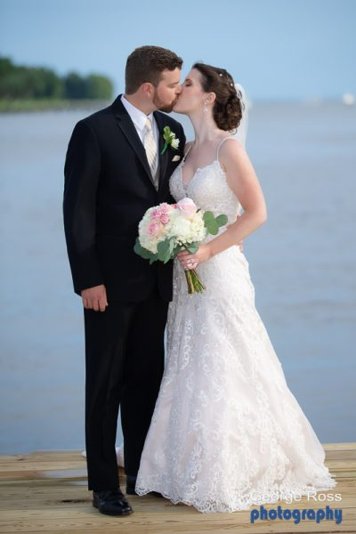 Bridie and  groom formal portrait at the end of a dock with the ocean behind them