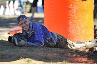 photographer smiling while lying in the mud while shooting an obstacle race