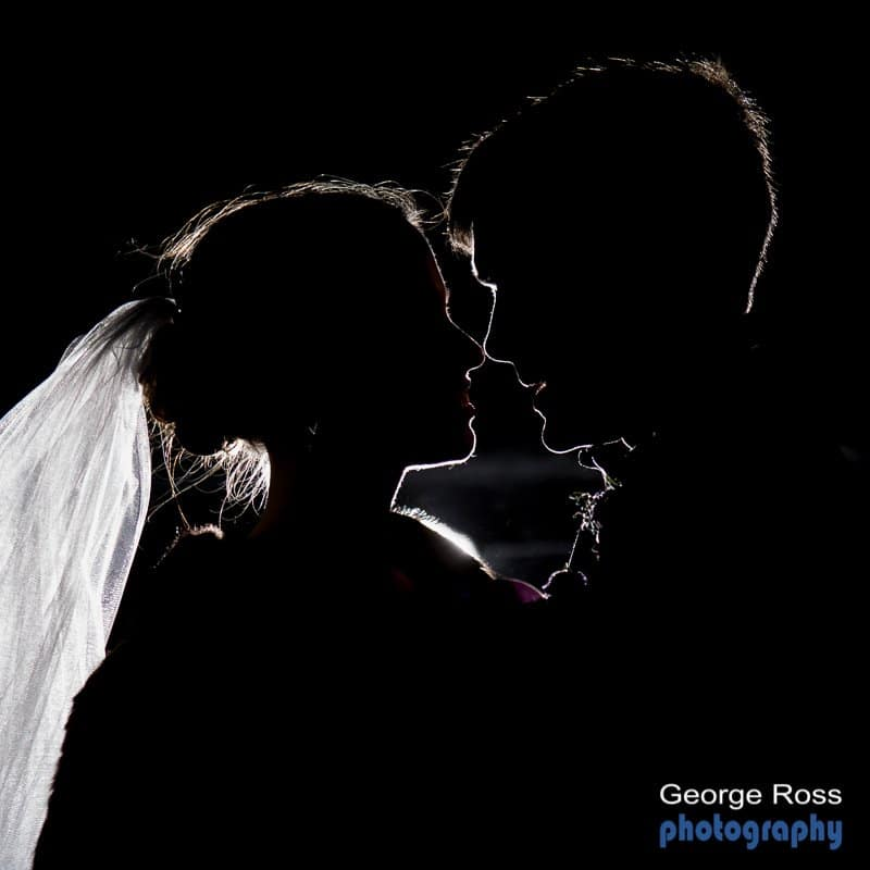 silhouette of a bride and groom on the beach at night
