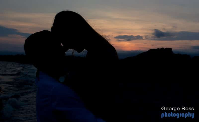 An engaged couple hugging at sunset
