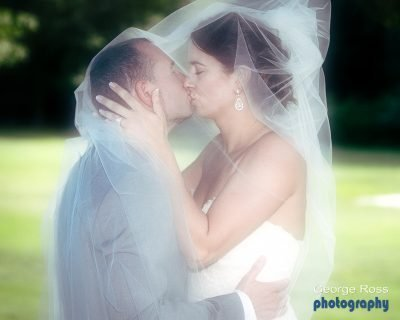 Bride and groom kissing a with a veil over both of them