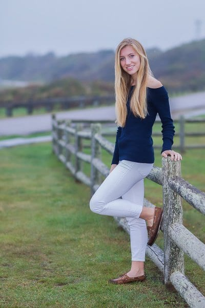 Blond female High School Senior photographed on a rustic fence