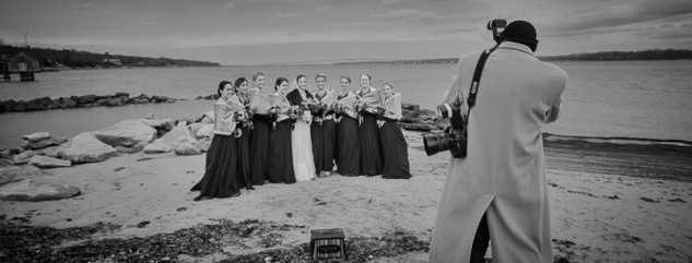 photographer, on a cold day, shooting a bridal party on bonnet shores, with jamestown bridge, rhode island, in the background