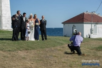 a wedding photographer taking a photo off the wedding party in front of point judith lighthouse, narraganset, rhode island