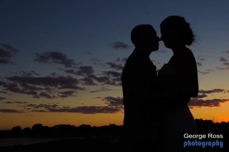 Harbor lights wedding at Sunset bride and groom French kiss