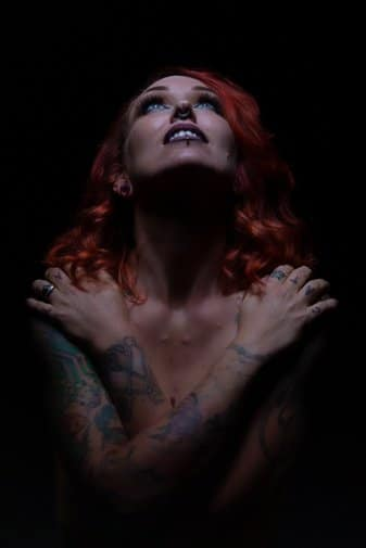 tattoo'd gothic model, implied nudity, in a low-key photo