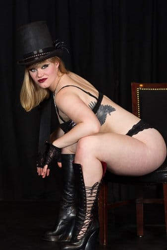 burlesque performer in on a chair wearing a top hat