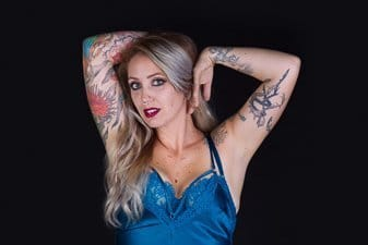 Tattoo'd model photographed against a black background
