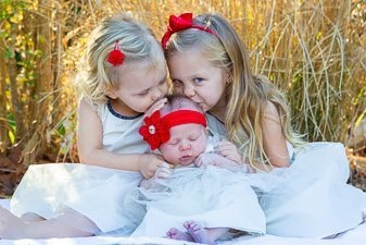 Two infant girls kissing their newborn baby sister.