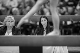 Two judges watch a gymnast on the balance beam