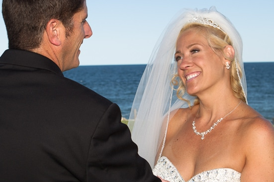bride looking at here groom beside the ocean