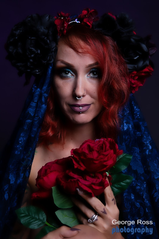 beautiful model with septum, draped in blue material holding roses