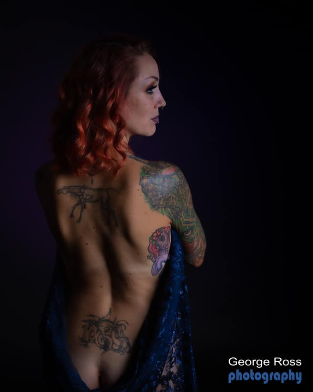 tattooed model with naked back holding blue fabric