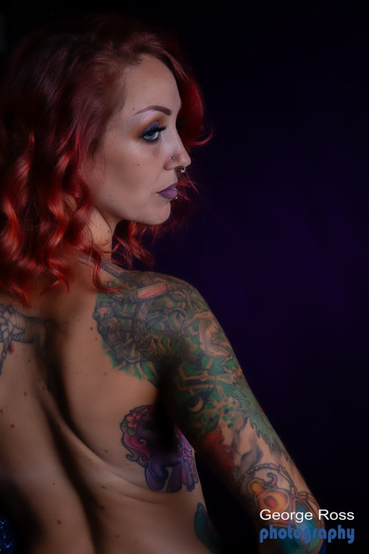 naked tattooed female model looking over her shoulder