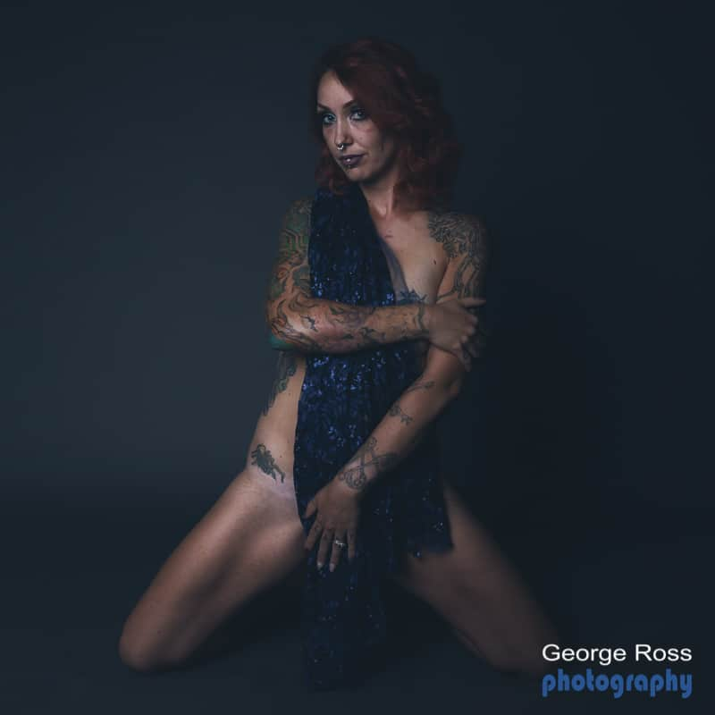 nude tattooed model with a septum. full frontal but covered with blue material