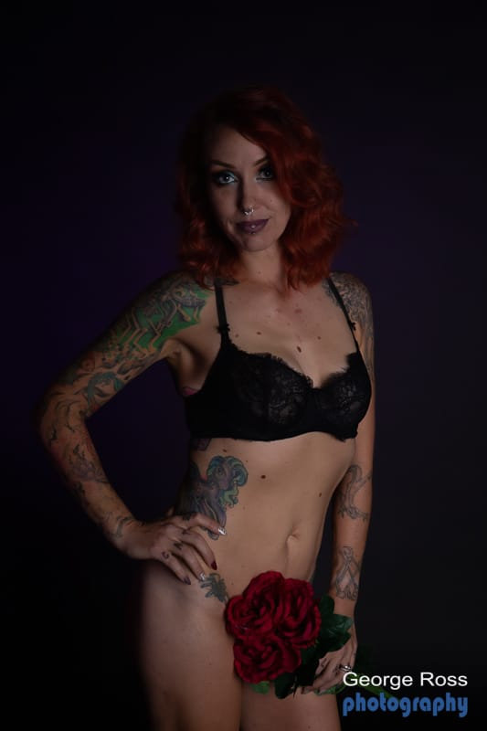 tattooed model nude from the wait down but using a rose to cover her vanity