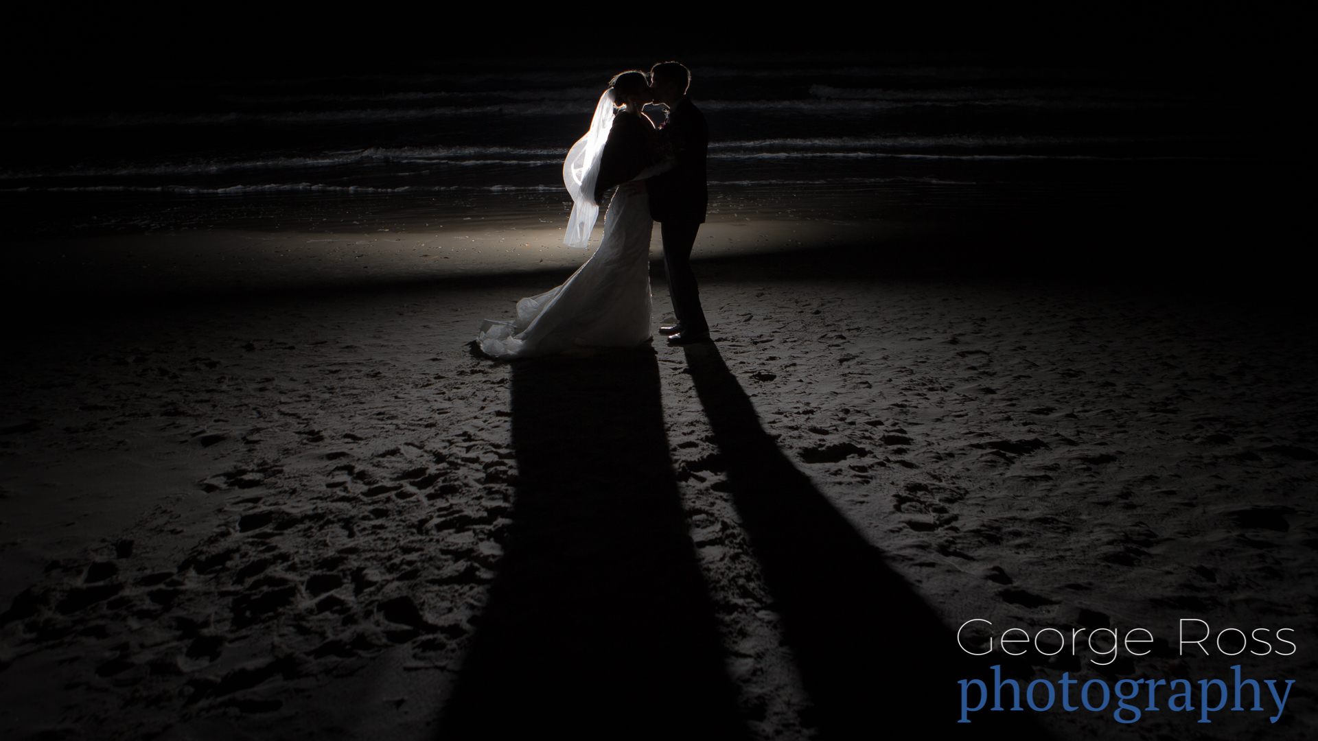 bride and groom on narragansett beach at night in the dark
