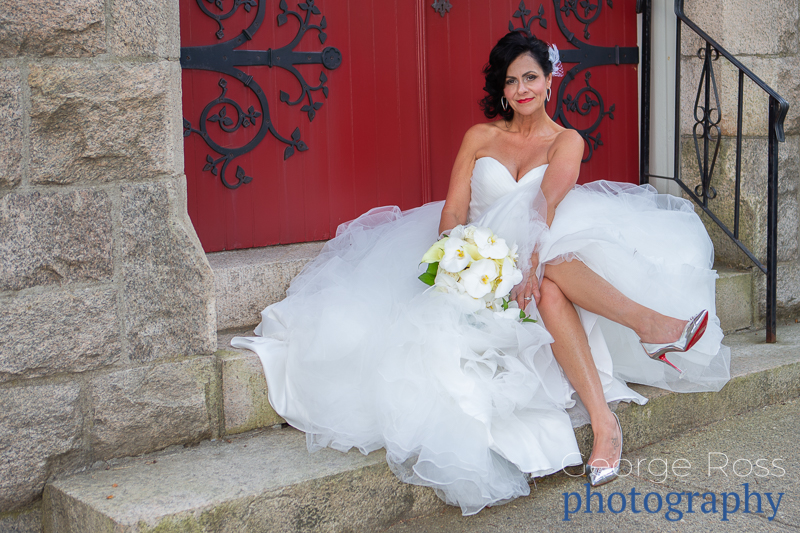 Bride sitting showing her Christian LouBoutin red soled shoes