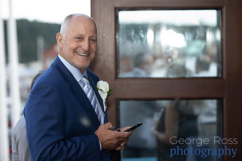 mature groom smiling looking at his phone