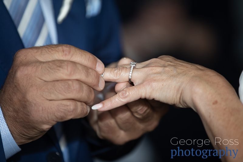 groom sliding the wedding ring on his bride's finger during the wedding ceremony