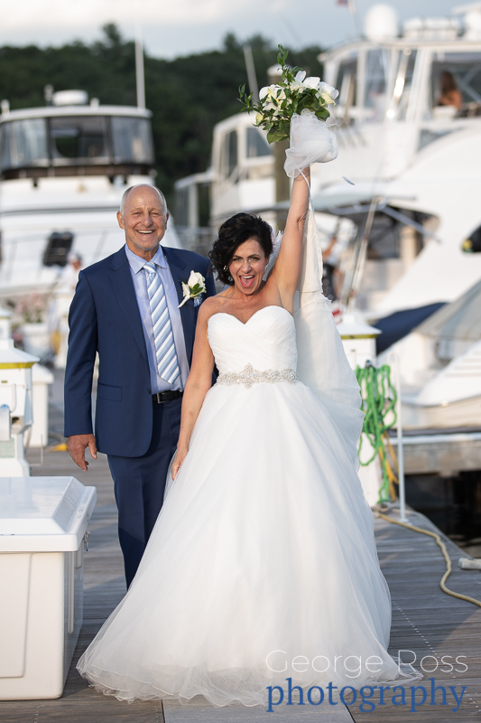 bride and groom on a pier beside a boat