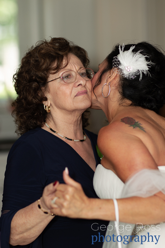 bride kissing her mother on the cheek