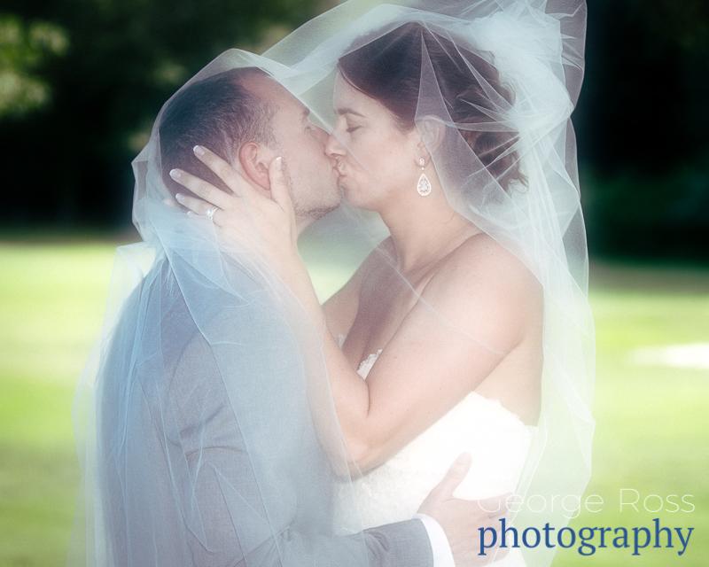bride kissing her groom under her veil