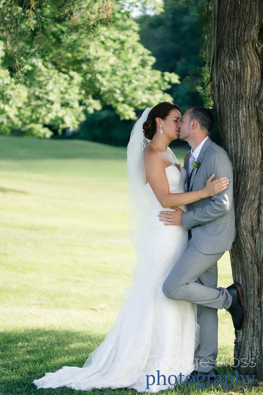 bride loving kisses her groom against a tree