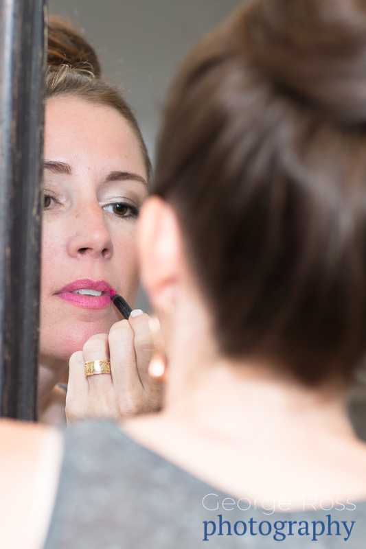 bridesmaid putting on lipstick in the mirror