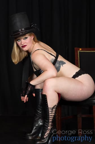 boudoir photo of woman in top hat sitting on a chair