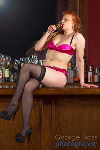 woman sipping wine sitting on a bar in pink lingerie