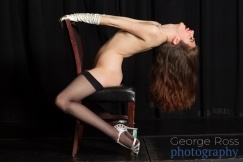 burlesque performer dancing on a chair while topless