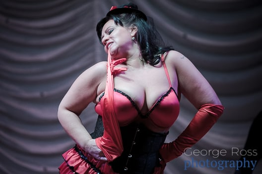 burlesque dancer pulling on her glove in her teeth