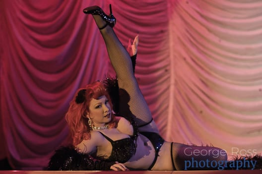 Diamond DeVille performs a burlesque dance with a red dress and is removing her red evening gloves