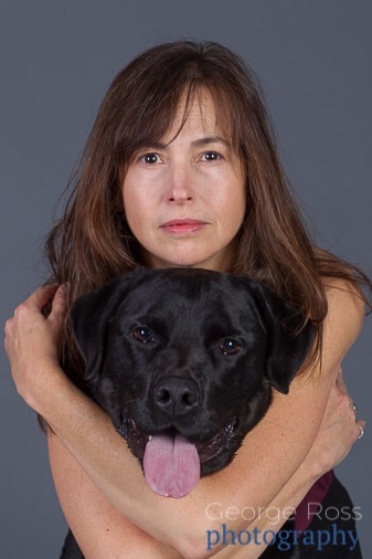 woman with long hair with arms hugging a black labrador
