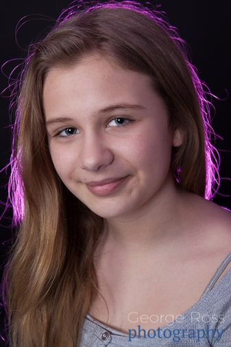 young female actress backlit with a pink light