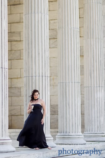 woman in black dress holding goblet in front of a building with pillars