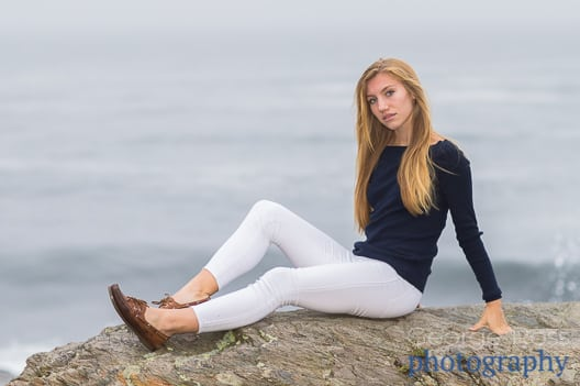 blond woman sitting on a rock at the ocean