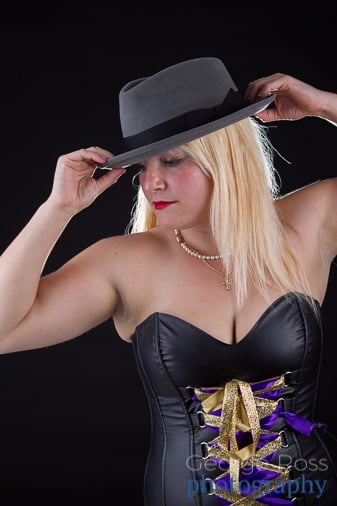 blond woman in corset wearing a hat