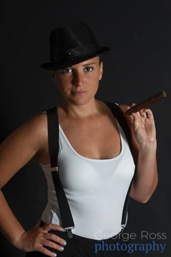 woman holding in a white vest and braces holding a cigar