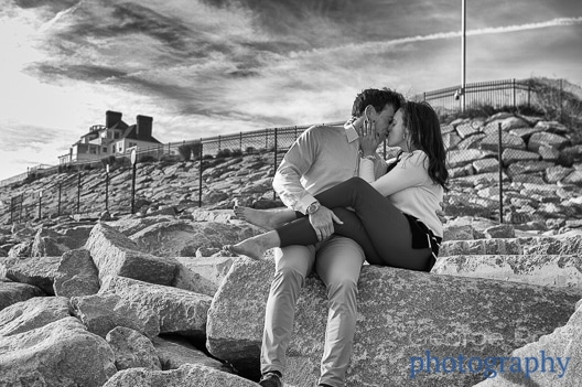 a couple in a French kiss after their happy proposal photoshoot at castle hill, rhode island