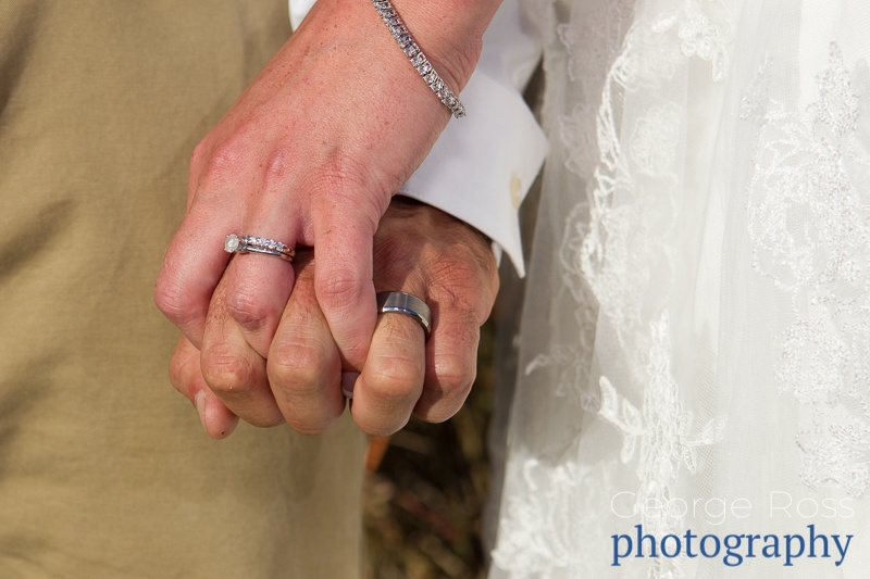 close up of bride and groom holding hands and showing of their wedding rings