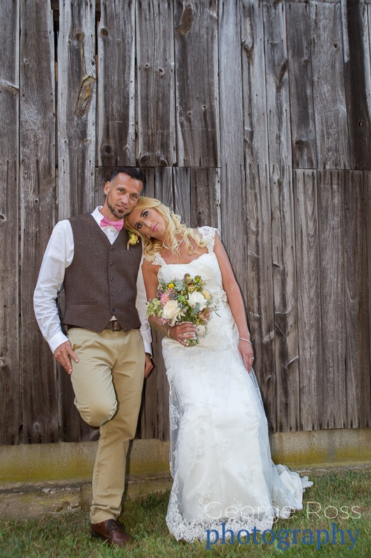 bride and groom leaning against a barn wall